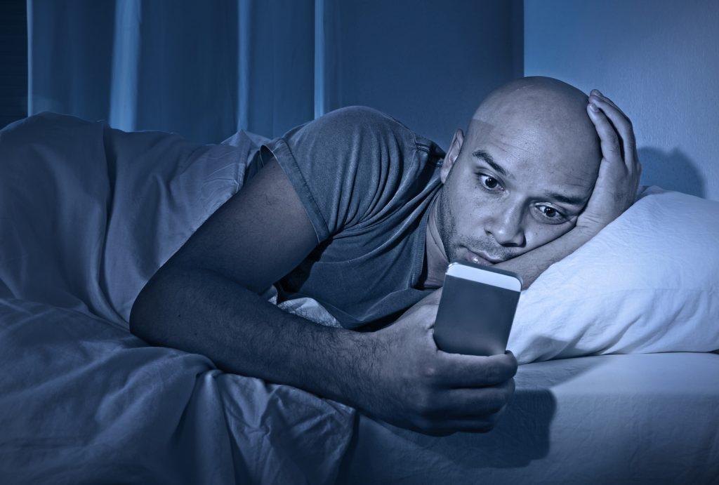 troubles du sommeil insomnie homme regardant son téléphone la nuit